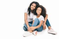 mooie gelukkige Afrikaanse Amerikaanse moeder en dochterzitting samen en glimlachend bij camera stock fotografie
