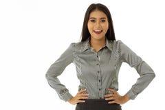 Mooie gelukkige Aziatische jonge die dame met met de handen in de zij wapens wordt bevonden stock afbeelding