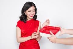 Mooie gelukkige Aziatische vrouw in rode kleding die giftdoos ontvangen Royalty-vrije Stock Afbeeldingen