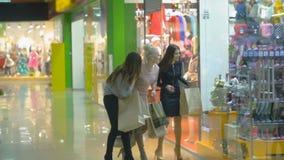 Mooie gelukkige dames die in een opslag met het winkelen zakken lopen Langzame Motie stock videobeelden