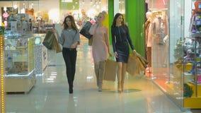 Mooie gelukkige dames die in een opslag met het winkelen zakken lopen Langzame Motie stock video