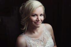 Mooie gelukkige en glimlachende bruid in huwelijkskleding die zich met een boeket van pionen in handen bevinden stock foto