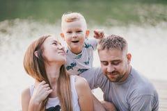 Mooie gelukkige familie die picknick hebben dichtbij meer Stock Afbeeldingen