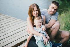 Mooie gelukkige familie die picknick hebben dichtbij meer Royalty-vrije Stock Foto's