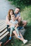 Mooie gelukkige familie die picknick hebben dichtbij meer Stock Foto
