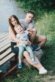 Mooie gelukkige familie die picknick hebben dichtbij meer Stock Foto's
