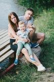 Mooie gelukkige familie die picknick hebben dichtbij meer Royalty-vrije Stock Afbeelding