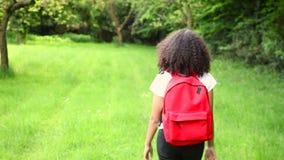 Mooie gelukkige gemengde de tiener vrouwelijke jonge vrouw die van het ras Afrikaanse Amerikaanse meisje met rode rugzak wandelen stock footage