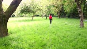 Mooie gelukkige gemengde de tiener vrouwelijke jonge vrouw die van het ras Afrikaanse Amerikaanse meisje met rode rugzak wandelen stock videobeelden