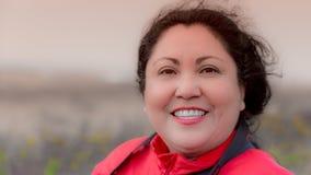 Mooie gelukkige glimlachende Latijnse vrouw op een prachtige winderige dag stock afbeelding