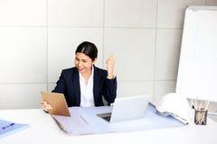 Mooie gelukkige jonge bedrijfsvrouw die in het bureau werken stock fotografie