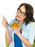 Mooie Gelukkige Jonge Spaanse Vrouw die een Plaat van Tomaat en Basil Penne Pasta houden Royalty-vrije Stock Afbeeldingen