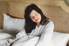 Mooie gelukkige jonge vrouw die in bed in de ochtend in hotelruimte of huisslaapkamer liggen Modieus donkerbruin meisje in het wi stock fotografie