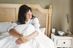 Mooie gelukkige jonge vrouw die in bed in de ochtend in hotelruimte of huisslaapkamer liggen Modieus donkerbruin meisje in het wi stock afbeeldingen