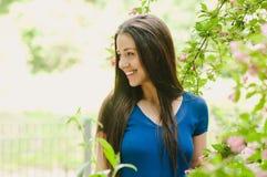 Mooie gelukkige jonge vrouw die bij bloemachtergrond glimlachen Stock Fotografie