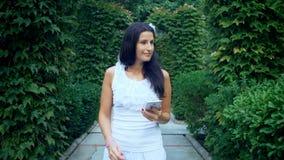 Mooie gelukkige jonge vrouw die een selfiefoto met slimme telefoon in openlucht in park op de zomerdag nemen stock footage