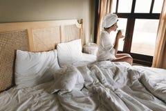 Mooie gelukkige jonge vrouw het drinken koffie in bed in hotelruimte of huisslaapkamer Modieus donkerbruin meisje in het witte ha royalty-vrije stock afbeelding