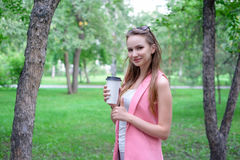 Mooie gelukkige jonge vrouw het drinken koffie in park Stock Afbeelding