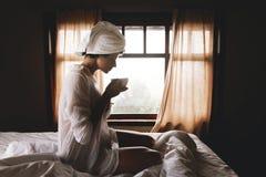 Mooie gelukkige jonge vrouw het drinken koffie of thee in bed in hotelruimte of huisslaapkamer Modieus donkerbruin meisje met wit royalty-vrije stock afbeeldingen