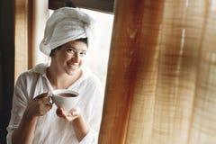Mooie gelukkige jonge vrouw het drinken koffie of thee, die bij groot houten venster in hotelruimte of huisslaapkamer zitten modi stock afbeelding