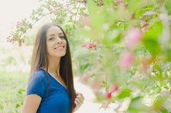 Mooie gelukkige jonge vrouw het glimlachen de zomer bloeiende bomen Stock Fotografie
