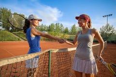 Mooie gelukkige meisjes die na het spelen van tennis en het schudden van handen glimlachen stock afbeeldingen