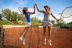 Mooie gelukkige meisjes die na het spelen van tennishoogte vijf glimlachen royalty-vrije stock foto's