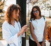 Mooie gelukkige meisjes die zich op een bushalte bevinden Royalty-vrije Stock Afbeeldingen