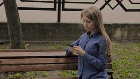 Mooie gelukkige meisjeszitting op een bank in een stadspark met een mobiele telefoon stock video