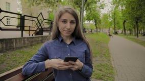 Mooie gelukkige meisjeszitting op een bank in een stadspark met een mobiele telefoon stock footage