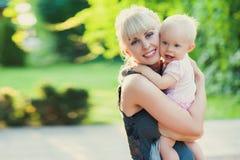 Mooie gelukkige moeder die babymeisje met de achtergrond van de liefde in openlucht zomer koesteren royalty-vrije stock foto's
