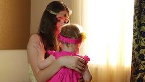 Mooie gelukkige moeder die babymeisje met liefde koesteren Mammaspelen met haar dochter in het kinderdagverblijf dichtbij het ven stock videobeelden