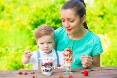 Mooie gelukkige moeder en haar kindjongen die gelaagd dessert in groene tuin in zonnige de zomerdag eten stock foto's