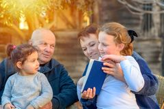 Mooie Gelukkige Oude paar en kleindochters die een boek samen in de aard lezen bij zonsondergang royalty-vrije stock foto