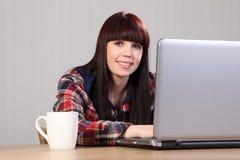 Mooie gelukkige student die thuiswerk op laptop doet Royalty-vrije Stock Foto