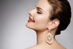 Mooie gelukkige vrouw in de oorringen van de luxemanier Diamant glanzende juwelen met brilliants Sexy retro stijlportret stock afbeelding