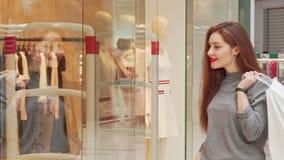 Mooie gelukkige vrouw die aan de camera glimlachen, die haar het winkelen zakken houden stock footage