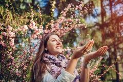 Mooie gelukkige vrouw die bloembloemblaadjes werpen die van bloeiende de lentetuin genieten Het hebben van pret royalty-vrije stock fotografie