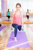 Mooie gelukkige vrouw die geschiktheidsoefening met gewicht in handen doen Royalty-vrije Stock Fotografie