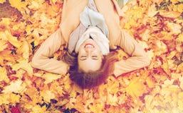 Mooie gelukkige vrouw die op de herfstbladeren liggen Stock Afbeelding