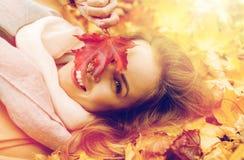 Mooie gelukkige vrouw die op de herfstbladeren liggen Stock Afbeeldingen