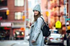 Mooie gelukkige vrouw die op stadsstraat lopen die toevallige grijze laag en hoed met een zak dragen Stock Afbeeldingen