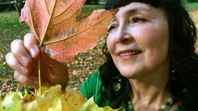 Mooie gelukkige vrouw in een groene kleding die en met gele bladeren in het de herfstpark sorteren spelen stock footage