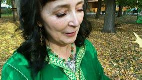 Mooie gelukkige vrouw in een groene kleding die en met gele bladeren in het de herfstpark sorteren spelen stock videobeelden
