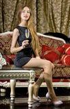 Mooie gelukkige vrouw op rode bank royalty-vrije stock fotografie