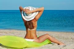 Mooie gelukkige vrouw in witte bikini met gele opblaasbare matras op het strand Royalty-vrije Stock Foto's