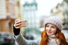 Mooie gembervrouw in de winterkleding die selfie op haar mo nemen royalty-vrije stock afbeeldingen