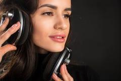 Mooie genietende van jonge vrouw die de muziek in draadloze hoofdtelefoon met gesloten ogen op donkere zwarte achtergrond luister royalty-vrije stock afbeeldingen