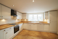 Mooie Gepaste Keuken in Modern Huis met Houten Vloer Stock Afbeeldingen