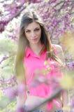 Mooie geschikte dame tussen bloesemboom in purpere kleur Royalty-vrije Stock Afbeelding